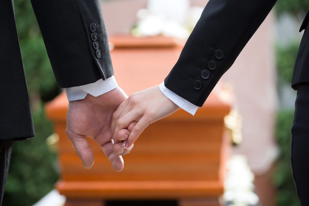 Man and women holding hands at a funeral. Overlooking a wooden coffin.