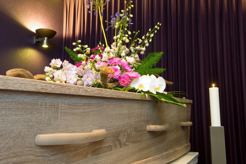 Wooden coffin with a pink and green flower arrangement on top.